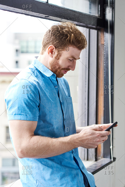 Male Messaging On Smartphone Against Window At Home