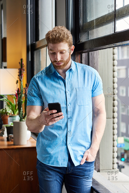 Man Texting On Mobile Phone At Home