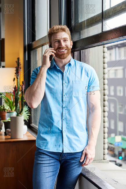 Smiling Man Talking On Smartphone At Home