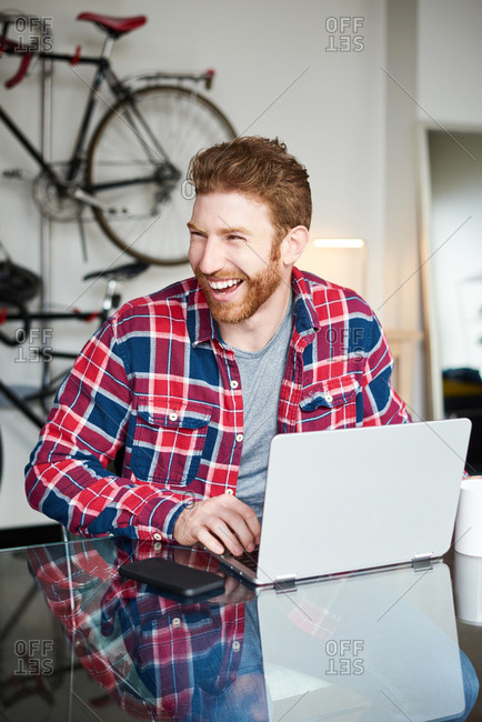 Cheerful Man Using Laptop At Table In House