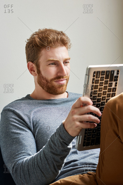 Handsome Man With Beard Using Laptop At Home