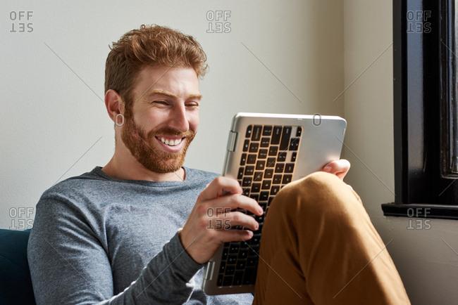 Smiling Man Using Laptop At Home