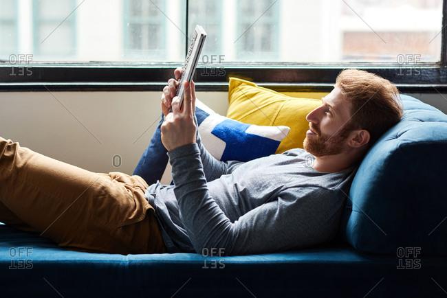 Handsome Man Using Digital Tablet On Sofa At Home