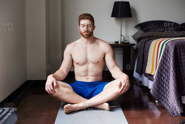 Shirtless Man Meditating With Closed Eyes In Bedroom At Home