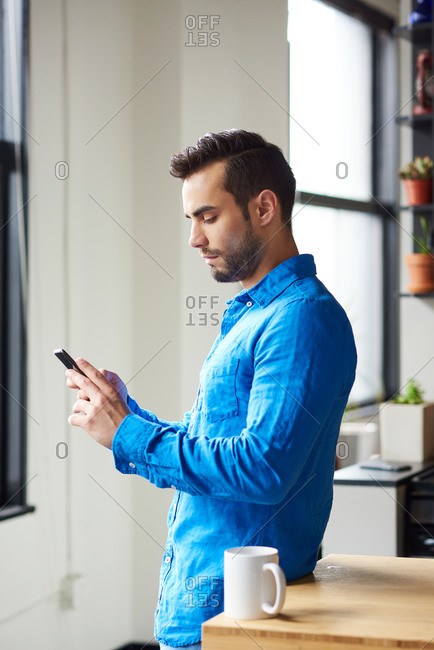 Man Using Mobile Phone While Standing At Table