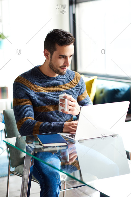 Man Having Coffee While Using Laptop At Home