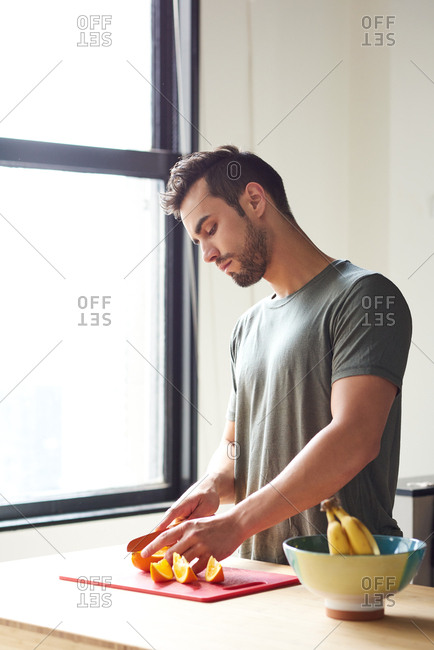 Man Cutting Fruits While Standing By Window In Kitchen