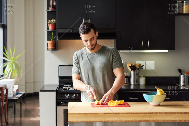 Man Cutting Fruits While Standing In Kitchen