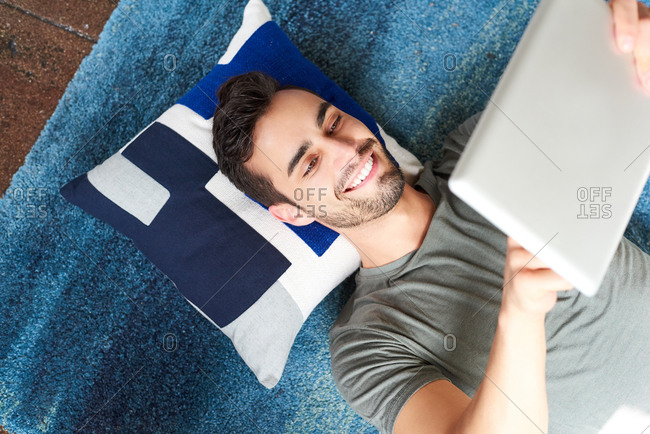 Man Using Digital Tablet While Lying At Home