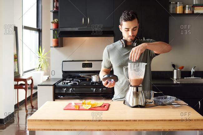 Man preparing smoothie in kitchen