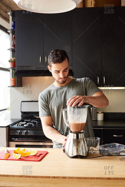 Man Preparing Smoothie While Using Blender On Kitchen Counter