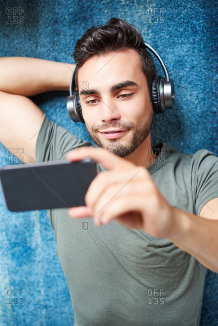 Man With Headphones Watching Movie On Smart Phone At Home