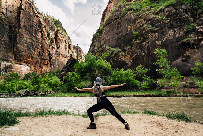 Woman Stretching Arms By River Against Mountains