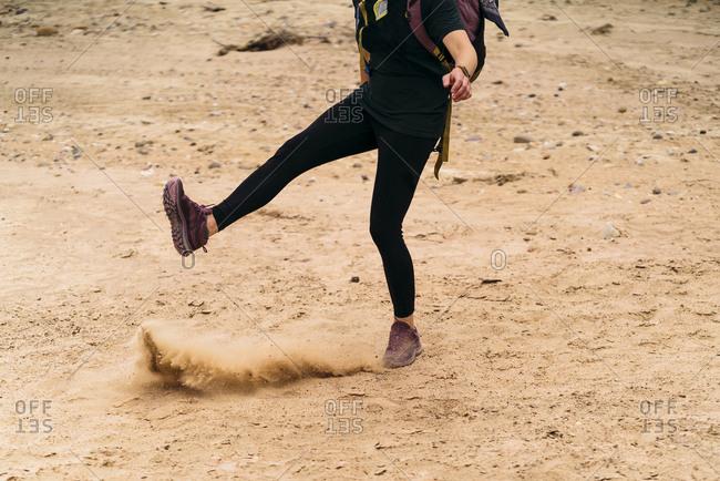 Traveler Kicking Sand While Enjoying In Desert