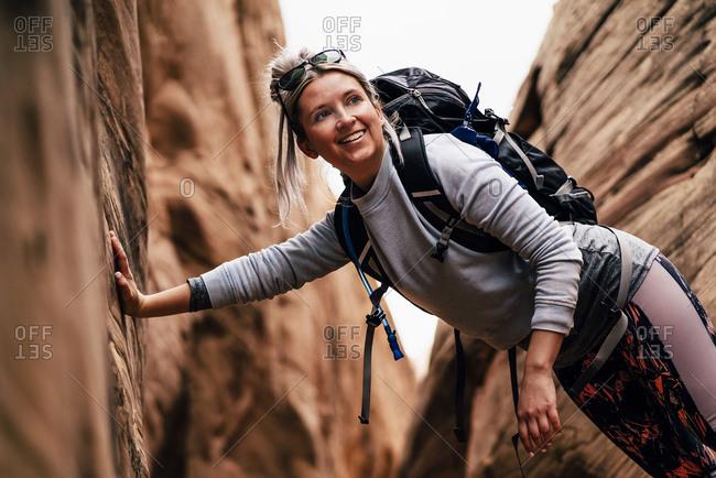 Smiling Backpacker Hiking Amidst Rock Formation In Utah