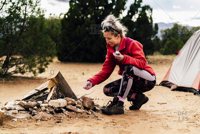 Smiling Woman Burning Campfire At Campsite In Desert
