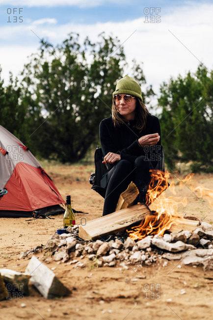 Thoughtful Woman Sitting At Campfire In Desert
