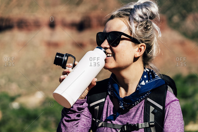 Hiker Drinking Water From Bottle While Hiking At National Park