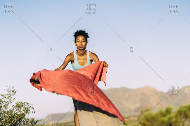 Woman Spreading Blanket On Field Before Exercise