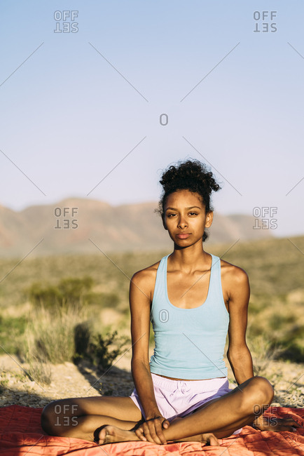 Portrait Of Woman Practicing Yoga On Blanket During Trip