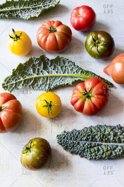 Overhead view of fresh heirloom tomatoes and kale on a kitchen counter