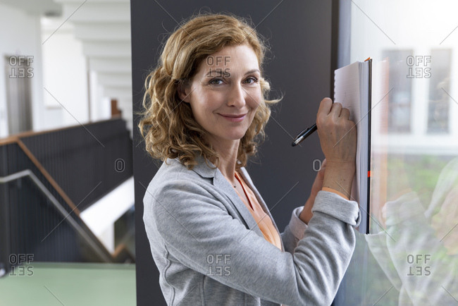 Portrait of smiling businesswoman taking notes at windowpane in office