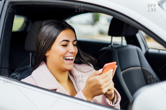 Businesswoman using smartphone in the car