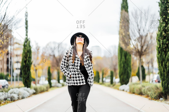 Smiling businesswoman wearing hat and sunglasses- looking up