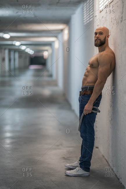 Barechested muscular athlete with rope leaning on wall