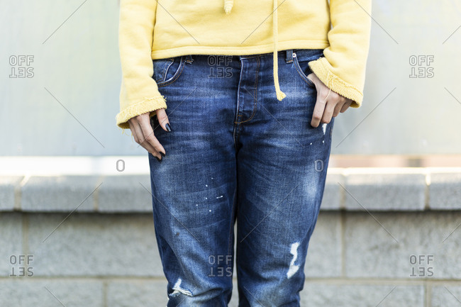 Young woman wearing old dark blue jeans- partial view