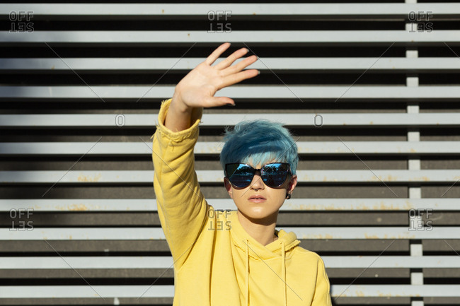 Portrait of young woman with dyed blue hair wearing mirrored sunglasses and yellow hooded jacket