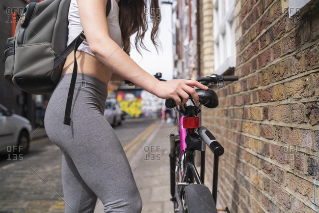 Young woman with bicycle and backpack in the city