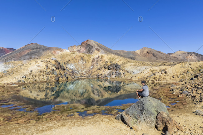 New Zealand- North Island- Male hiker relaxing at Emerald Lakes in North Island Volcanic Plateau