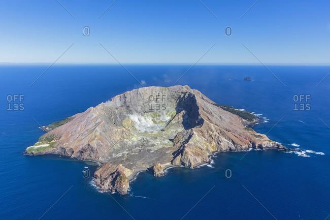 New Zealand- North Island- Whakatane- Aerial view of White Island (Whakaari) surrounded by blue waters of Pacific Ocean