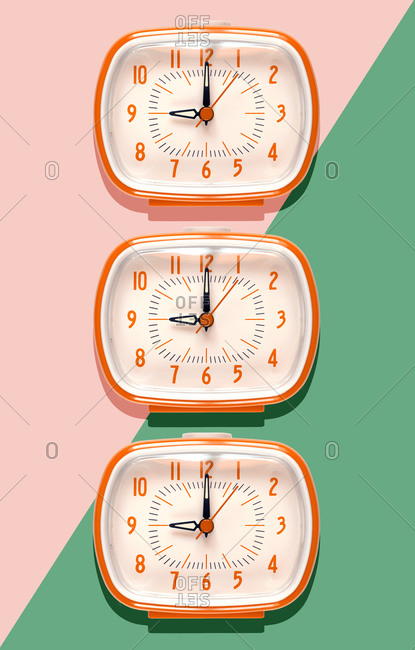 3D Illustration- row of orange alarm clocks at nine o'clock on pink and mint green background