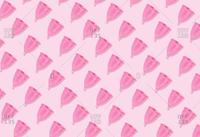 Eco-friendly and reusable pink menstrual cup pattern on pink background