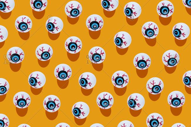 Fake scary eyeballs for Halloween on orange background