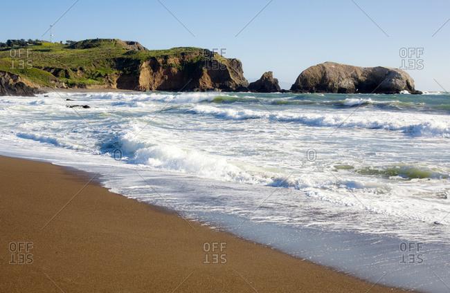 USA- California- San Francisco- Waves brushing sandy coastal beach of Marin Headlands