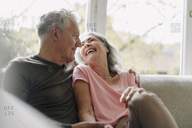 Happy senior couple relaxing on couch at home