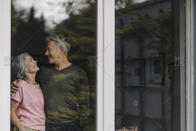 Happy senior couple behind windowpane of their home