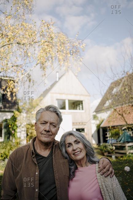 Portrait of senior couple in garden of their home in autumn