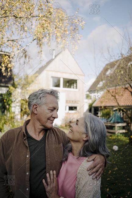 Happy senior couple in garden of their home in autumn