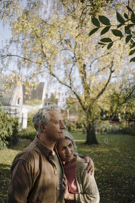 Senior couple in garden of their home in autumn