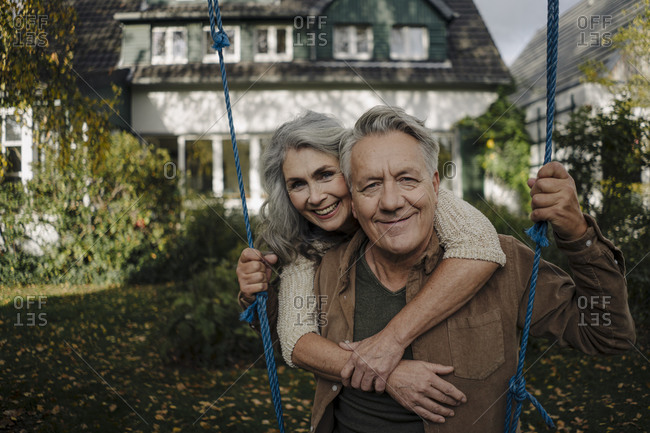 Portrait of a happy woman embracing senior man on a swing in garden