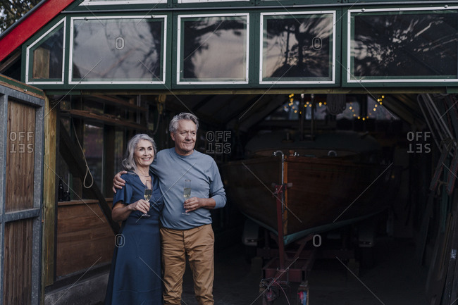Senior couple standing in front of boathouse with glass of champagne