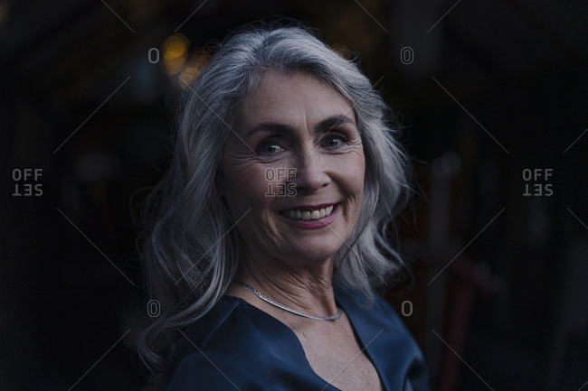 Portrait of a smiling mature woman outdoors at night