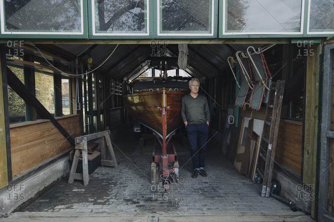 Senior man standing at wooden boat in a boathouse