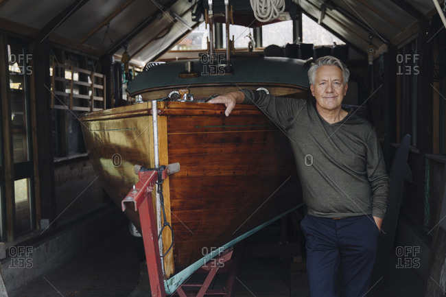 Portrait of a proud senior man at wooden boat in a boathouse