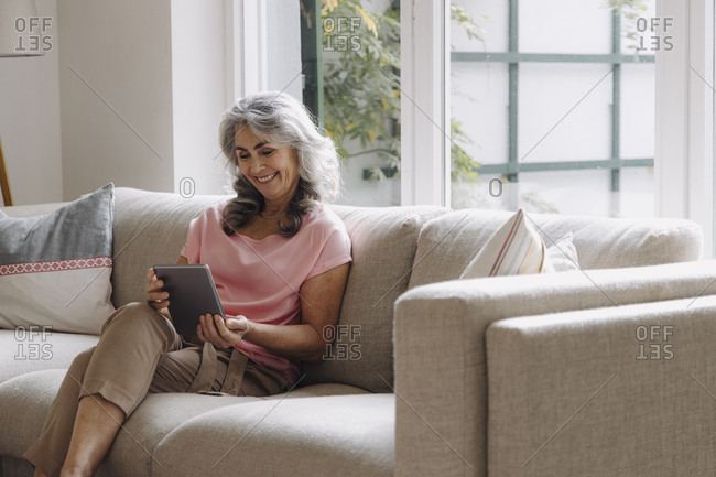 Smiling mature woman using tablet sitting on couch at home
