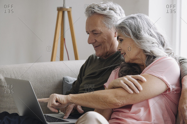 Senior couple with laptop relaxing on couch at home